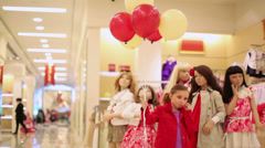 Girl posing with balloons backdrop of mannequins in clothes Stock Footage