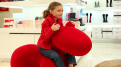 Little girl in a red jacket riding a red toy like a pony Stock Footage