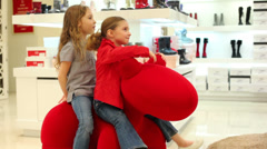 Two beautiful little girl riding a red toy like a pony Stock Footage