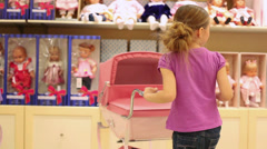 Girl stroller rolls on the background of shelves with toys Stock Footage