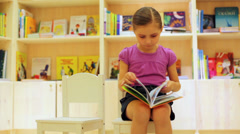 Little girl reading a book un the store sitting on a white chair Stock Footage