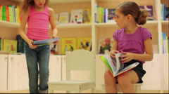 Little girl reading book in store sitting and other chooses book Stock Footage