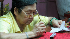 Old Vietnamese woman writing on a paper Stock Footage