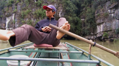 Paddler in Tam Coc, Vietnam paddle a tourist boat with his feet. Stock Footage