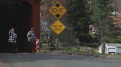 Couple in matching plaid taking pics of covered bridge Stock Footage