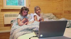Two five years old sisters watching cartoons before going to sleep in bedroom - stock footage