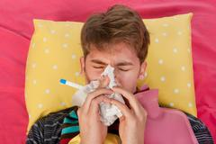 very ill man is blowing his nose - stock photo