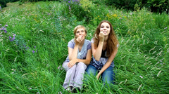 Cheery  mother and daughter fun with spikelets in the mouth on a green meadow - stock footage