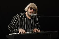 Singer accompanies himself on electric piano Stock Photos
