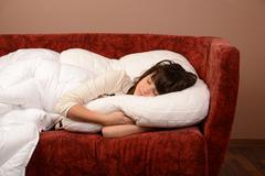 happy young girl slipping on sofa - stock photo