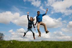 Happy jumping couple Stock Photos