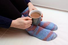 Woman holding a hot drink, wearing warm knitted socks Stock Photos