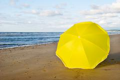 Stock Photo of yellow parasol at the beach
