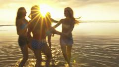 Group of Five Teenage Girls Dancing In The Water At The Beach At Sunset Stock Footage