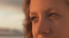 Kaunis teini-ikäinen tyttö etsii kohti aurinkoa rannalla auringonlaskun aikaan Arkistovideo