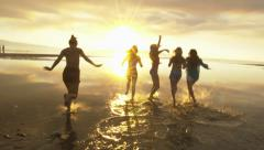 Group of Five Teenage Girls Run Into The Water, Celebrate On The Beach At Sunset Stock Footage