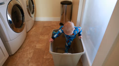A toddler playing in the laundry room Stock Footage