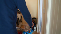A single father doing laundry with his toddler Stock Footage