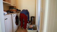 Single father doing the laundry with his toddler boy Stock Footage