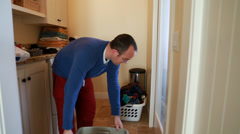 A single father doing the laundry with his toddler boy Stock Footage