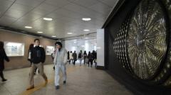 People walking by the Eye of Shinjuku, Tokyo Stock Footage