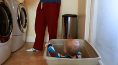 A little boy playing while father does laundry Stock Footage