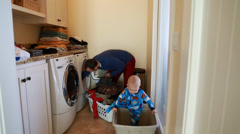 father doing the laundry with his toddler - stock footage