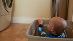 A boy falls over in laudry basket Stock Footage
