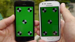 Two Cell Phone, touch screen, held by hands. Comparison. Green screen Chroma Key Stock Footage