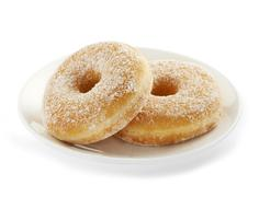 two tasty donuts served on a white plate - stock photo