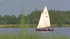 Small sailing boat on Dutch peat lake + zoom out reed land Stock Footage