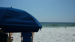 Wide shot beach with quarter view of chairs and umbrella Stock Footage