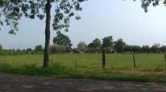 Polder landscape,  road and thatched saxon farmhouse in The Netherlands Stock Footage