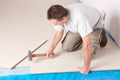 worker installing a laminated flooring - stock photo