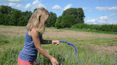 Farmer woman girl make wreath crown from blue cornflower flowers Stock Footage