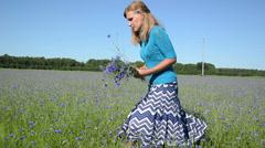 Turn view of girl pick blue cornflower flowers in summer field Stock Footage