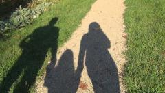 Family with Child Walking on Meadow in Park, Pov Shadow of People Enjoy Summer Stock Footage
