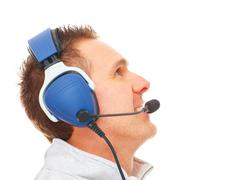 pilot with headset looking aside - stock photo