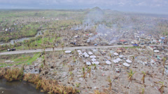 Flight over devastated outskirts of a town with refugee tents Stock Footage