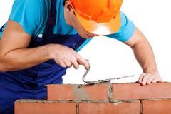 Handyman installing red brick Stock Photos