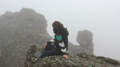 Lady resting on stone admiring mountain rocks in fog Stock Footage