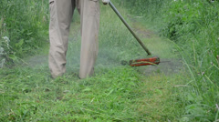 Closeup worker farmer cutting grass in garden with weed trimmer Stock Footage