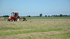 Tractor heavy machine equipment ted hay dry grass in field Stock Footage