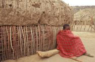 Stock Photo of Africa, Kenya, masai boy sitting outside village hut