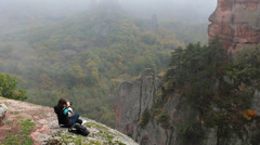 Young woman resting on a rock in the mountains Stock Footage