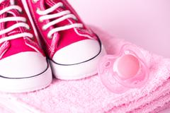 Dummy and baby shoes Stock Photos