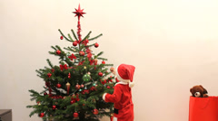 Baby dressed in Santa Claus play with  bell ornaments from Christmas tree  Stock Footage