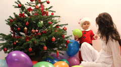 Baby dressed in Santa Claus together with mother near fir tree, many balloons Stock Footage