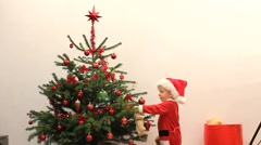 Baby boy dressed in Santa Claus hold teddy bear arrange Christmas tree - stock footage