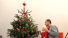 Father give a bell decoration to baby dressed in Santa Claus from Christmas tree Stock Footage